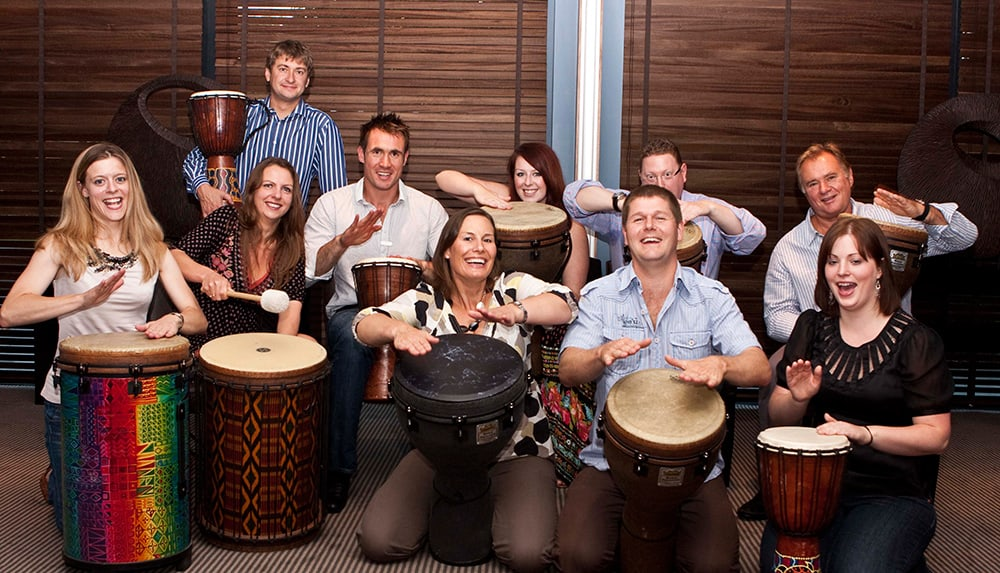 People drumming in team building session